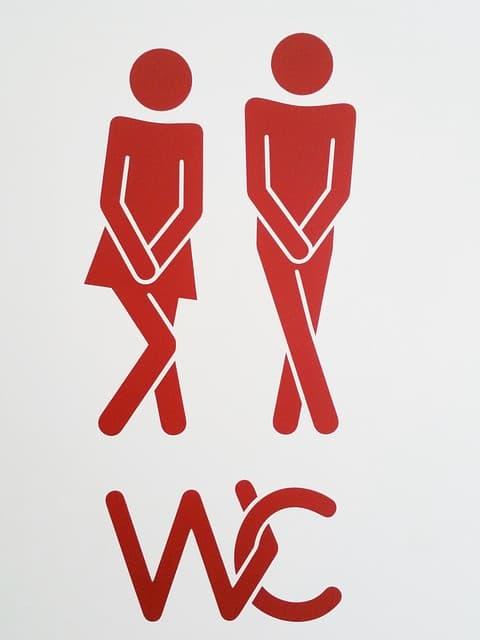 men women toilet sign holding it