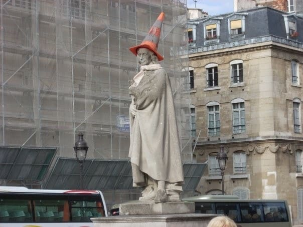 traffic cone on statue head in paris